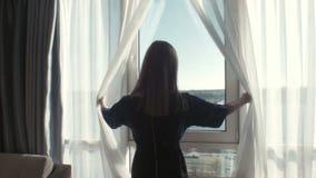 妇女拉开在旅馆神色的帷幕在窗口 股票录像