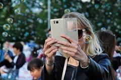 妇女拍与她的电话的照片在肥皂泡背景在节日`启发`在莫斯科 库存照片