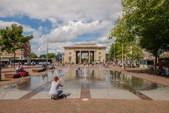 妇女拍充当喷泉在一个历史城市门前面的一个正方形在阿姆斯特丹她的孩子的照片 库存图片