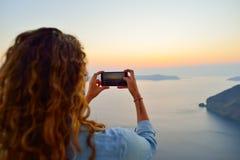 妇女拍圣托里尼海岛照片  免版税图库摄影