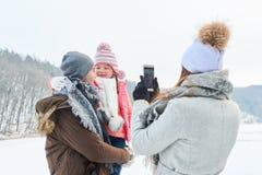 妇女拍父亲和女儿的照片 库存图片