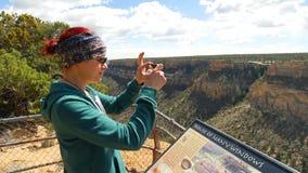 妇女拍Anasazi与她的智能手机的窑洞的照片 免版税图库摄影