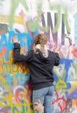 妇女拥抱五颜六色的街道画墙壁 库存图片