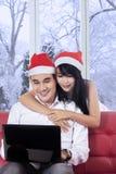 妇女拥抱她的男朋友,当使用膝上型计算机时 库存图片