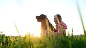 妇女拥抱狗在日落和笑,有坐草和休息本质上的宠物的女孩 图库摄影