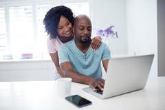 妇女拥抱的人,当使用膝上型计算机时 免版税库存照片