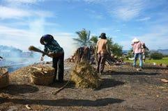 妇女拾起烹调的壁炉边出于烧伤区域。 免版税库存图片