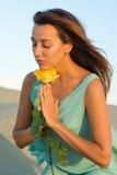 妇女拿着一朵黄色玫瑰 免版税库存图片