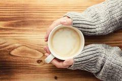 妇女拿着一杯咖啡在一张木桌上的 免版税库存照片