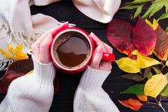 妇女拿着一杯红色咖啡在黑暗的木桌上的` s手 免版税库存照片