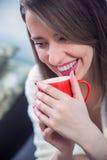 妇女拿着一杯红色咖啡的` s手 美好的冬天修指甲 免版税库存图片