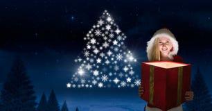 妇女拿着不可思议的礼物和雪花圣诞树的圣诞老人仿造发光在冬天夜的形状 库存照片