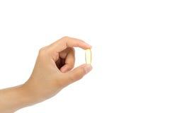 妇女拿着与Ω 3和维生素D健康饮食概念的` s手鱼油胶囊 免版税图库摄影