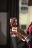 妇女拿着与一朵玫瑰的松弛酒精桃红色coctail在上面 免版税库存图片