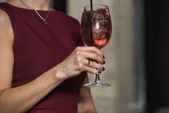 妇女拿着与一朵玫瑰的松弛酒精桃红色coctail在上面 库存图片