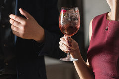 妇女拿着与一朵玫瑰的松弛酒精桃红色coctail在上面 免版税图库摄影