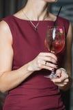 妇女拿着与一朵玫瑰的松弛酒精桃红色coctail在上面 免版税库存照片