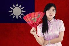 妇女拿着与台湾旗子的一个爱好者  库存图片