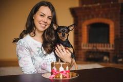 妇女拿着与狗蛋糕infront的玩具狗在生日聚会 免版税图库摄影