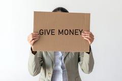 妇女拿着与题字的一副横幅给金钱 库存照片