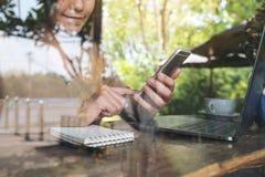 妇女拿着和看巧妙的电话的` s手的特写镜头图象,当使用膝上型计算机时 免版税库存照片
