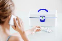 妇女拿着在天线罩包装的药片和叫对医生 免版税库存图片