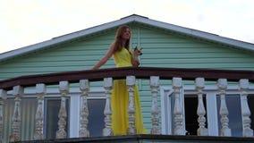 妇女拿着在她的胳膊的一条小狗并且去沿栏杆的阳台 股票录像