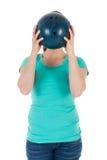 妇女拿着在她的头之前的一个保龄球 免版税库存图片
