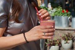 妇女拿着在玻璃透明mugon的可口新鲜的草莓白色木桌 免版税图库摄影