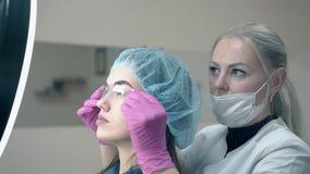 妇女拿着塑料统治者在女孩眉头显示刺字 股票录像