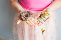 妇女拿着多福饼和一卷测量的磁带的` s手特写镜头  概念吃健康 饮食 免版税库存图片