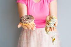 妇女拿着多福饼和一卷测量的磁带的` s手特写镜头  概念吃健康 饮食 免版税库存照片