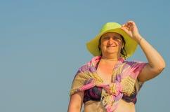 妇女拿着她的在风的帽子 库存照片