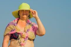 妇女拿着她的在风的帽子 免版税库存图片
