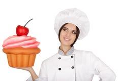 妇女拿着巨大的杯形蛋糕的点心师 免版税库存照片