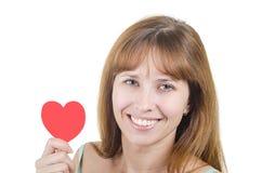 妇女拿着心脏手中并且微笑 库存图片