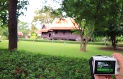 妇女拿着拍的`手一个印象深刻的泰国样式传统葡萄酒房子的照片,泰国一台照相机 库存照片