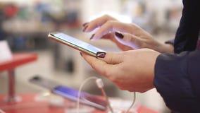 妇女拿着智能手机手中 拿着智能手机的女性手特写镜头视图,使用触摸屏幕 股票视频