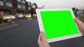 妇女拿着有一个绿色屏幕的一台空白的片剂个人计算机您自己的习惯内容的 股票视频