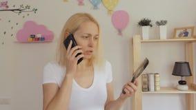 妇女拿着有下落的头发子线的一把梳子和谈话在电话 股票视频