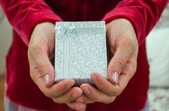 妇女拿着有丝带的白色礼物盒 免版税库存照片