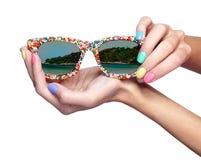 妇女拿着有海海滩反射的o太阳镜 免版税库存图片