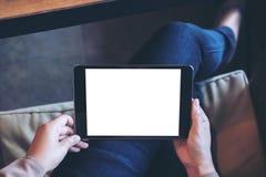 妇女拿着有空白的白色屏幕的` s手的大模型图象黑片剂个人计算机在大腿有地板背景 库存图片