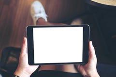 妇女拿着有空白的白色屏幕的` s手的大模型图象黑片剂个人计算机在大腿 库存图片