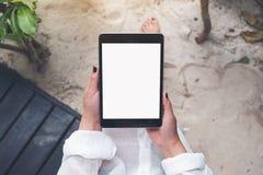 妇女拿着有空白的白色桌面屏幕的` s手黑片剂个人计算机有沙子和海滩背景 图库摄影