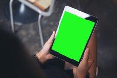 妇女拿着有空白的绿色屏幕的` s手的大模型图象黑片剂个人计算机在大腿 免版税库存照片