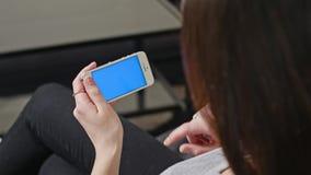 妇女拿着有蓝色屏幕的智能手机 免版税库存照片