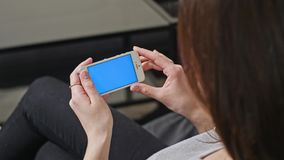 妇女拿着有蓝色屏幕的智能手机 库存图片
