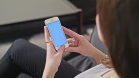 妇女拿着有蓝色屏幕的智能手机 库存照片