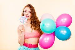 妇女拿着棒棒糖糖果和气球 免版税库存图片